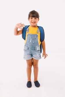 Klein meisje met zwart haar gekleed in een blauwe tuinbroek en een t-shirt, met een rugzak klaar voor terug naar school, zwaaiend, op witte achtergrond.