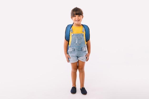 Klein meisje met zwart haar gekleed in een blauwe tuinbroek en t-shirt, met een rugzak klaar voor terug naar school, op witte achtergrond