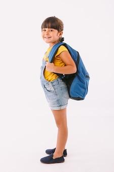 Klein meisje met zwart haar gekleed in een denim overall en een blauw t-shirt, met een rugzak klaar om terug te gaan naar school, aan haar kant, op witte achtergrond