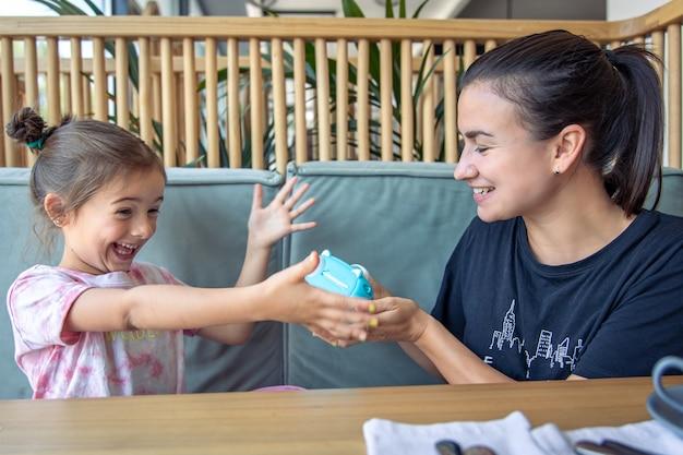 Klein meisje, moeder en een speelgoed digitale camera voor kinderen om direct foto's te printen.