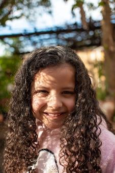 Klein meisje, mooi meisje met krullend haar in de schaduw van bomen gelukkig, kleine scherptediepte, selectieve focus.