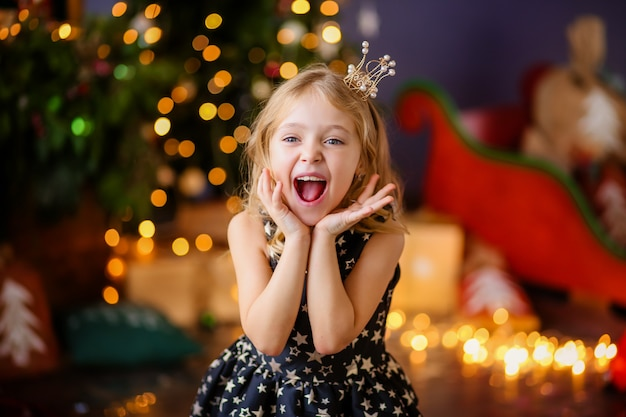 Klein meisje naast de kerstboom