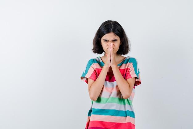 Klein meisje omklemde handen in gebedspositie in t-shirt, spijkerbroek en kijkt ontevreden, vooraanzicht.