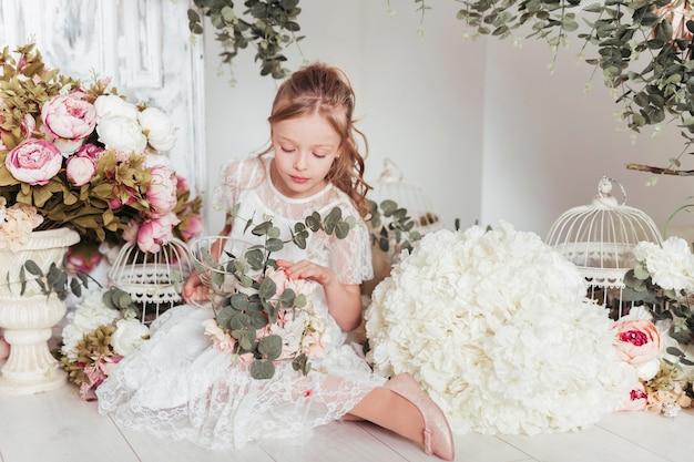 Klein meisje omringd door bloemen