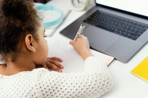 Klein meisje online school bijwonen thuis met behulp van laptop