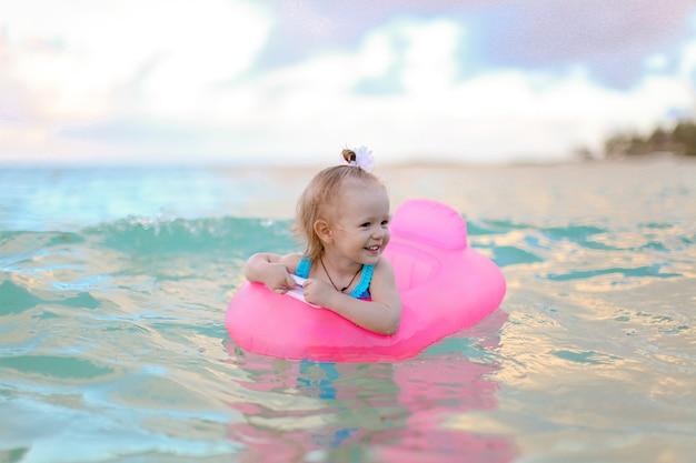 Klein meisje ontspannen op opblaasbare luchtbed in de zee