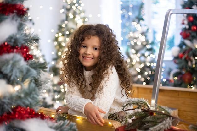 Klein meisje op de achtergrond van kerstbomen en verlichting. vrolijk kerstfeest en een gelukkig nieuwjaar