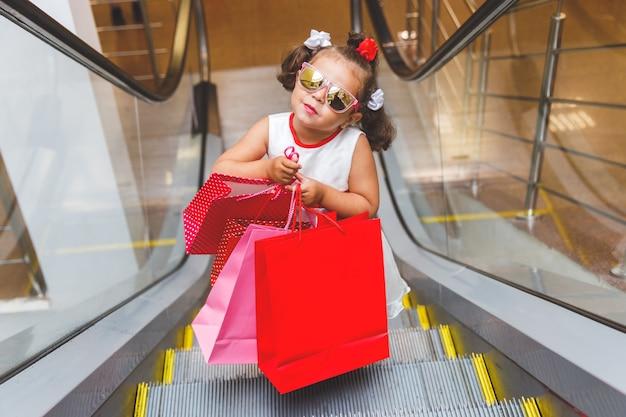 Klein meisje op de roltrap in het winkelcentrum met aankopen