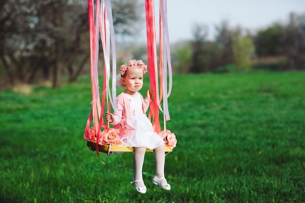Klein meisje op de schommel, klein meisje in het park, schattig klein meisje, klein meisje