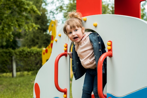 Klein meisje op de speelplaats. gelukkig lachend kind spelen op buiten. baby lacht, schreeuwt emotioneel, vreugde en een gelukkige jeugd.