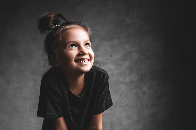 Klein meisje op een grijze achtergrond. portret in prachtige kleuren