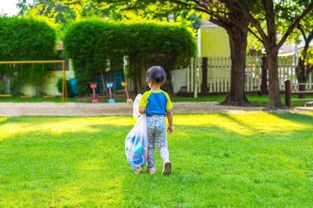 Klein meisje op een speelplaats. kind buiten spelen in de zomer.