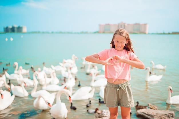Klein meisje op het strand met prachtige zwanen