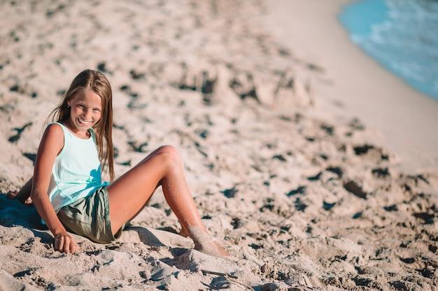 Klein meisje op het strand speelt met zand bij zonsondergang