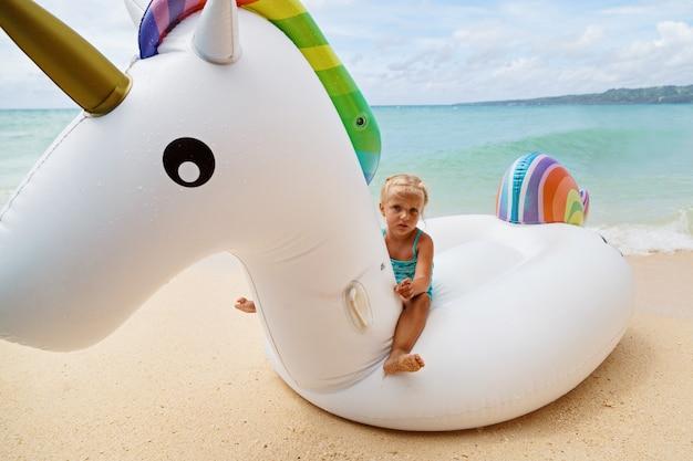 Klein meisje op opblaasbare eenhoorn op de zee