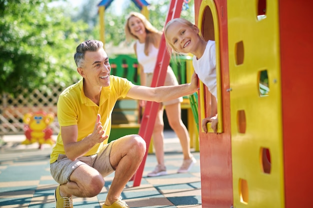 Klein meisje op speelplaats met haar ouders