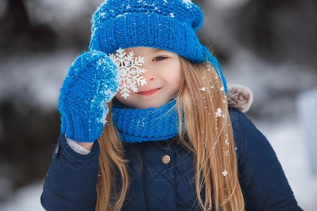 Klein meisje op winter achtergrond met sneeuwvlok