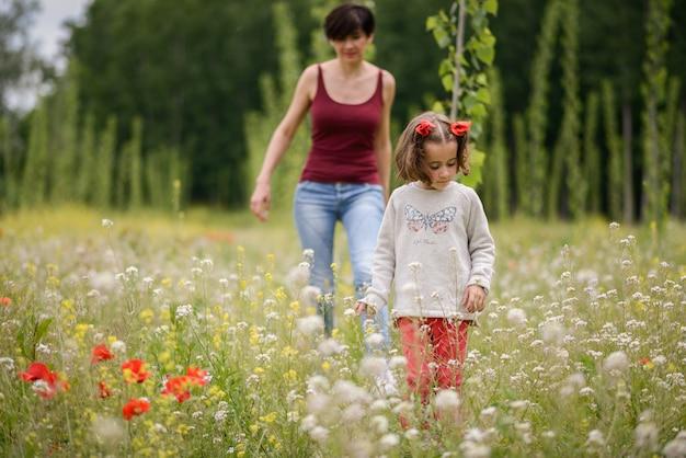Klein meisje op zoek naar bloemen in de wei