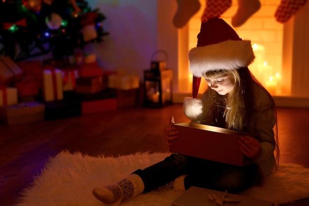 Klein meisje opent kerstcadeau in woonkamer