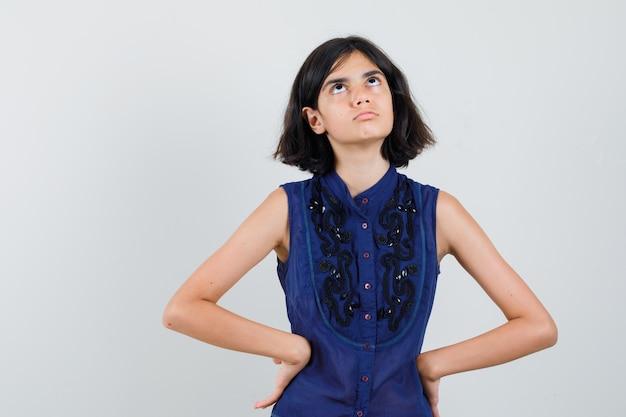 Klein meisje opzoeken in blauwe blouse en nieuwsgierig kijken,