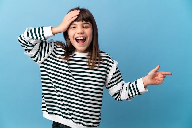 Klein meisje over geïsoleerde achtergrond verrast en wijzende vinger naar de zijkant