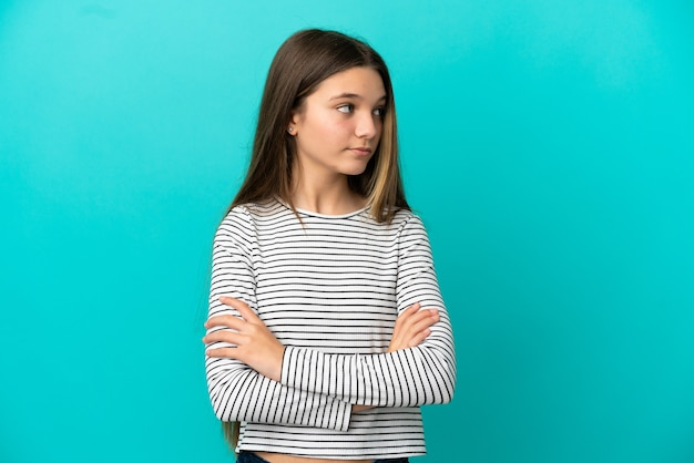 Klein meisje over geïsoleerde blauwe achtergrond die de armen gekruist houdt