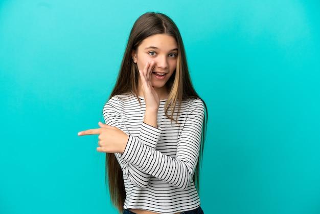 Klein meisje over geïsoleerde blauwe achtergrond die naar de zijkant wijst om een product te presenteren en iets te fluisteren