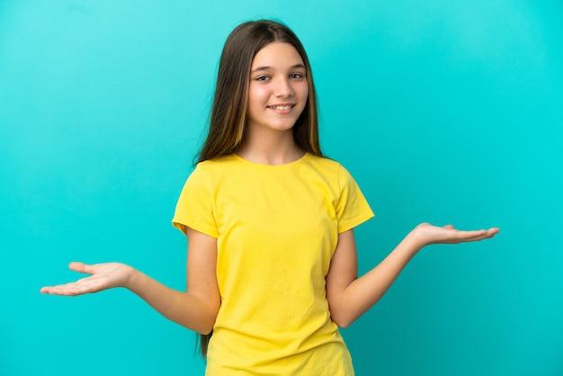 Klein meisje over geïsoleerde blauwe achtergrond gelukkig en glimlachend