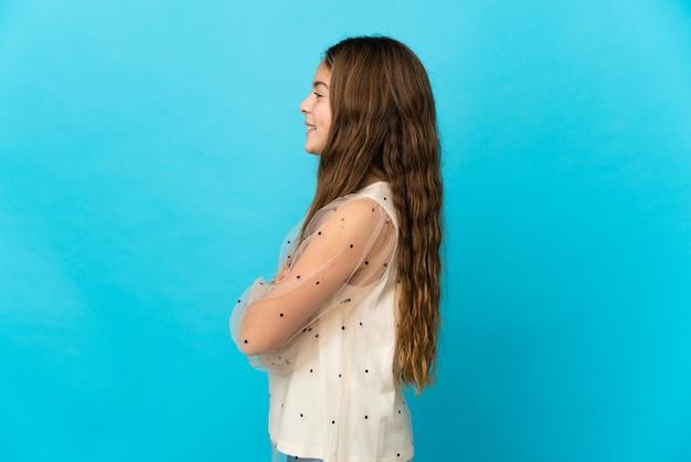 Klein meisje over geïsoleerde blauwe achtergrond in zijpositie