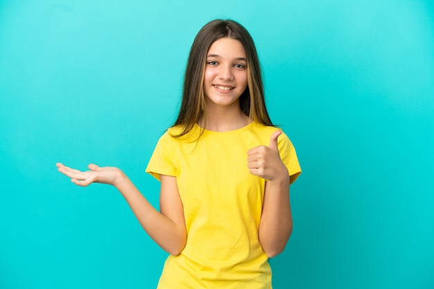 Klein meisje over geïsoleerde blauwe achtergrond met copyspace denkbeeldig op de palm om een advertentie in te voegen en met duimen omhoog