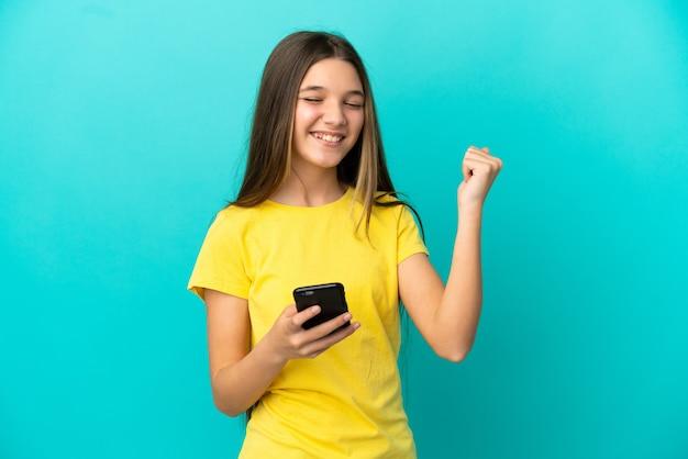 Klein meisje over geïsoleerde blauwe achtergrond met telefoon in overwinningspositie