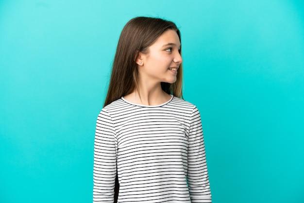 Klein meisje over geïsoleerde blauwe achtergrond op zoek naar kant