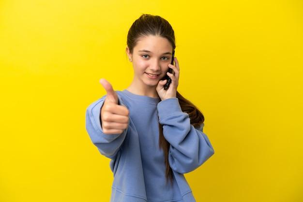 Klein meisje over geïsoleerde gele achtergrond die een gesprek voert met de mobiel terwijl ze duimen omhoog doet