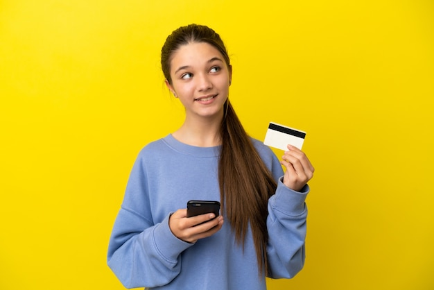Klein meisje over geïsoleerde gele achtergrond kopen met de mobiel met een creditcard terwijl ze denken