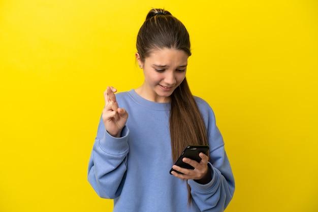 Klein meisje over geïsoleerde gele achtergrond met behulp van mobiele telefoon met vingers over elkaar