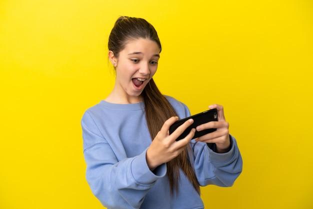 Klein meisje over geïsoleerde gele achtergrond spelen met de mobiele telefoon