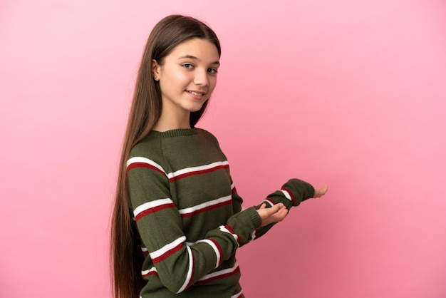 Klein meisje over geïsoleerde roze achtergrond die haar handen naar de zijkant uitstrekt om uit te nodigen om te komen