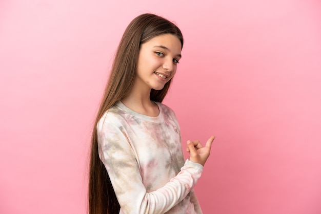 Klein meisje over geïsoleerde roze achtergrond die terug wijst