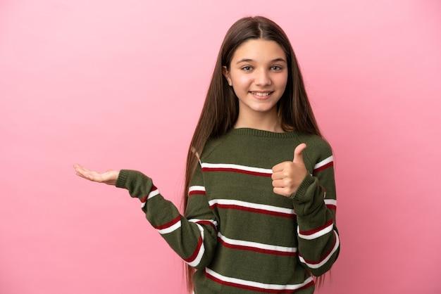 Klein meisje over geïsoleerde roze achtergrond met copyspace denkbeeldig op de palm om een advertentie in te voegen en met duimen omhoog