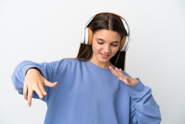 Klein meisje over geïsoleerde witte achtergrond muziek luisteren en dansen