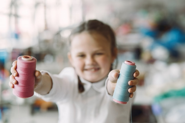 Klein meisje permanent in de fabriek met een draad