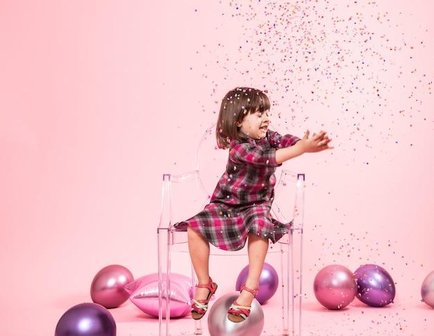 Klein meisje plezier met confetti. het concept van feest en plezier.