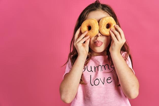 Klein meisje poseert met een paar donuts op haar ogen op een roze muur