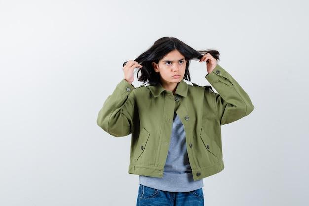 Klein meisje poseert terwijl ze haar oren regelt in jas, t-shirt, spijkerbroek en er gefocust uitziet. vooraanzicht.