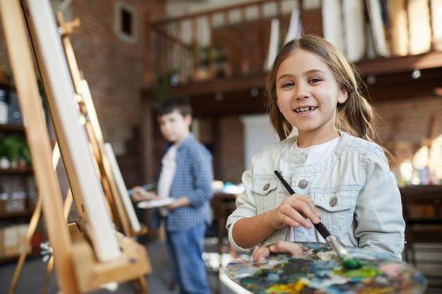 Klein meisje poseren in de kunst klasse