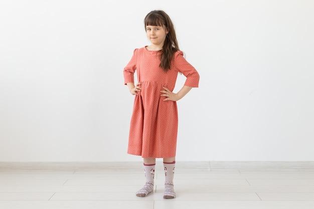 Klein meisje poseren in kleding in de studio