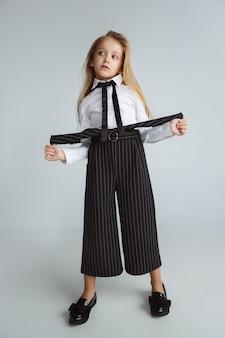 Klein meisje poseren in schooluniform met rugzak op witte muur