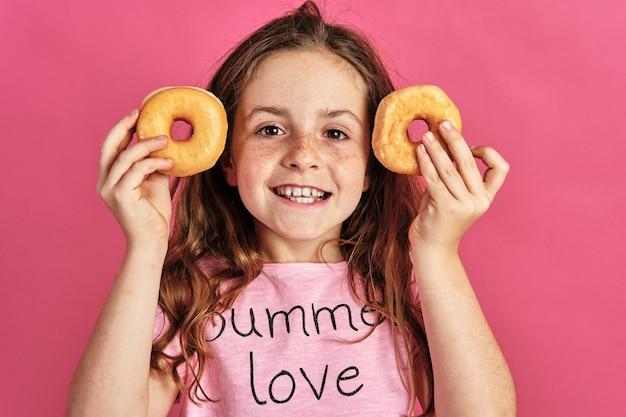 Klein meisje poseren met een paar donuts op een roze