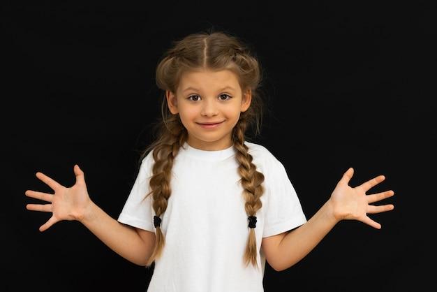 Klein meisje poseren op een zwarte achtergrond.