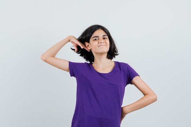 Klein meisje poseren terwijl het aanraken van haar in t-shirt en ziet er leuk uit